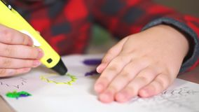Boy teenager draws a plastic figure yellow leaf. He uses a 3D pen.