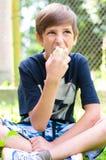 Boy teenager eating green apple. Sitting on garden grass outdoors Stock Photos