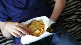 Boy teenager eating potato chips with hands on sofa at home.fast food unhealthy food stock video footage