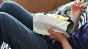 Boy teenager eating potato chips with hands on sofa at home.fast food unhealthy food stock footage