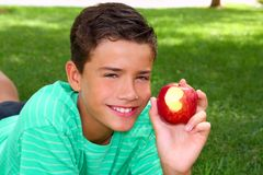 Boy teenager eating red apple on garden grass. Boy teenager eating red apple laying on garden grass outdoors Royalty Free Stock Photo