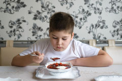 Boy teenager eating soup at  kitchen table Royalty Free Stock Images