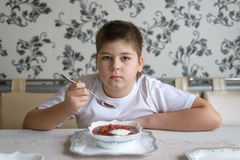 Boy teenager eating soup at  kitchen table Stock Images