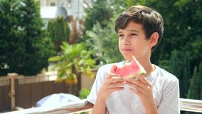 Boy teenager eating a watermelon outside on a background of greenery and sky. Slow motion. stock footage