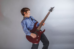 Boy teenager European appearance playing guitar on. A gray background Stock Photography