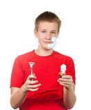 The boy, the teenager the first time tries to have a shave and is confused. Royalty Free Stock Photography