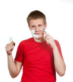 The boy, the teenager the first time tries to have a shave and is confused. Stock Images