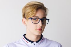 Boy teenager in glasses and white shirt poses. In white studio, close up royalty free stock images
