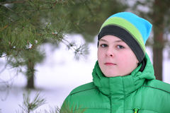 Boy teenager in  green jacket at  winter pine forest Royalty Free Stock Image
