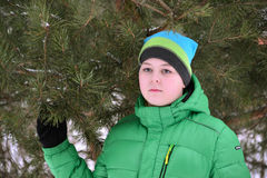 Boy teenager in  green jacket at  winter pine forest Stock Images