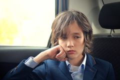 A boy is a teenager with a long hair in a classic suit in the car. royalty free stock photo