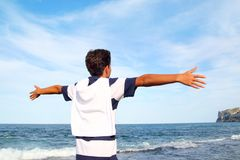 Boy teenager open arms rear view looking blue sea Stock Images