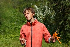Young man eating a carrot. Boy teenager in orange jacket eating carrots in a green garden Stock Photography