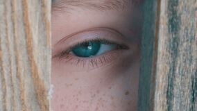 Boy teenager peeking into the crack in fence or doorway close up view. Boy teenager peeking into the crack in the fence or doorway close up view stock video