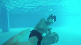 Boy teenager pool underwater playing in the war. The boy shoots underwater from the weapon gun. Boy teenager pool underwater playing in the war. The boy shoots stock footage