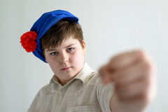 Boy teenager in Russian national cap with cloves showing a fist Royalty Free Stock Photo