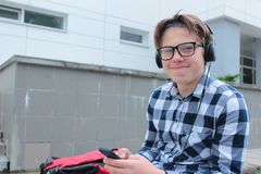 Boy teenager schoolboy or student in a shirt, smiles in glasses, listens to music on the phone. Red backpack, school background Stock Photo