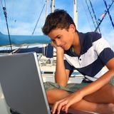 Boy teenager seat on boat marina laptop computer Royalty Free Stock Photos