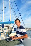 Boy teenager seat on boat marina laptop computer Stock Images