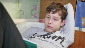 Boy teenager sick with conjunctivitis inflamed eye on face large face reads book lying on bed