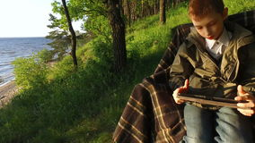 Boy teenager sitting on a chair on the shore of a large lake. Teen Boy enthusiastically playing a computer game on a Tablet PC. stock video footage