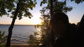 Boy teenager sitting on a chair on the shore of a large lake. Teen Boy enthusiastically playing a computer game on a Tablet PC. stock footage
