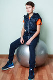 Boy teenager sitting on fitball. Fitness child in sportswear. Royalty Free Stock Images