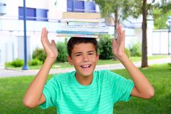 Boy teenager student holding head stacked books Royalty Free Stock Image