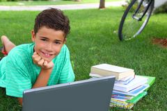 Boy teenager studying laying green grass garden Stock Photography