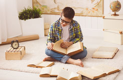 Boy teenager studying, reading books, preparing for exams at hom Royalty Free Stock Images