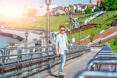 Boy teenager in sunglasses and jeans riding a skateboard and makes selfie on river embankment royalty free stock image