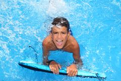 Boy teenager surfboard splashing blue water Stock Photos