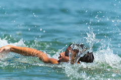 boy teenager swims in the sea with big splashes Stock Images
