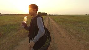 Boy teenager tourist drinking water from a plastic bottle in nature. Boy homeless vagabond drink water thirst Stock Image