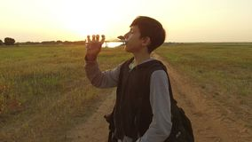 Boy teenager tourist drinking water from a plastic bottle in nature. Boy homeless vagabond drink water thirst Stock Photos