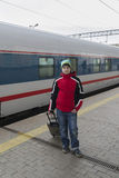 Boy teenager with  travel bag near a train Royalty Free Stock Images