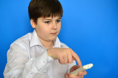 Boy teenager with  TV remote control on a blue background Royalty Free Stock Images