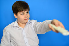 Boy teenager with  TV remote control on a blue background Stock Image