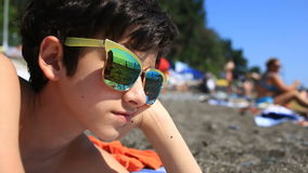 Boy a teenager wearing sunglasses on the beach, a beach with vacationers reflected in glasses. Boy a teenager wearing sunglasses on the beach, a beach with stock footage