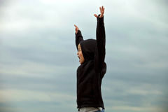 Boy teenager winner in a sports jacket raised his hands and shouts. Boy teenager tourist stands sideways to the camera. Man hands up and shouting. He is pleased Royalty Free Stock Images