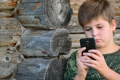 Boy teenager writes sms standing by awooden wall Stock Photography