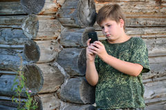 Boy teenager writes sms standing by awooden wall Stock Photo