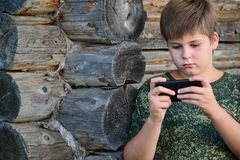 Boy teenager writes sms standing by awooden wall Royalty Free Stock Photo