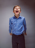 Boy teenager yells looking up on a gray background Royalty Free Stock Photography