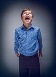 Boy teenager yells looking up on gray background Royalty Free Stock Photography