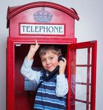 Boy with telephone. Cute little boy in the red telephone box Stock Photo