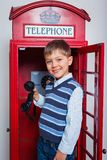 Boy with telephone. Cute little boy in the red telephone box Stock Photography