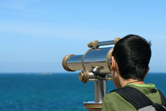 The boy and the telescope. A boy watching trhu a telescope Royalty Free Stock Images