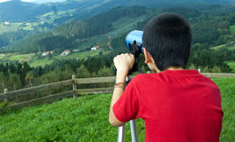 Boy and telescope. A boy watching trhu a telecope Stock Images