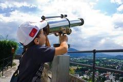Boy with telescope. Boy with cap looking through a telescope near Salzburg, Austria Royalty Free Stock Image